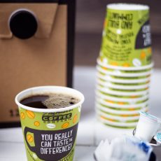 Cup of coffee surrounded by sugar packets, creamer cups, coffee cups and a 12 cup box of coffee
