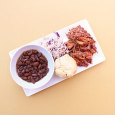 BBQ Chicken, Cornbread, Baked Beans and Coleslaw on a white plate
