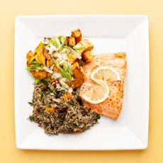 Salmon Filet with wild rice and roasted vegetables on a white plate