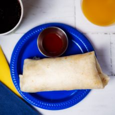 Breakfast Burrito on blue plate with a small side of hot sauce, cup of coffee, cup of juice, maize and blue napkins