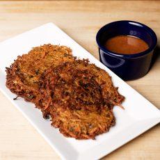 Sweet Potato Latkes on a white platter with a side of peanut sauce in a blue ramekin.
